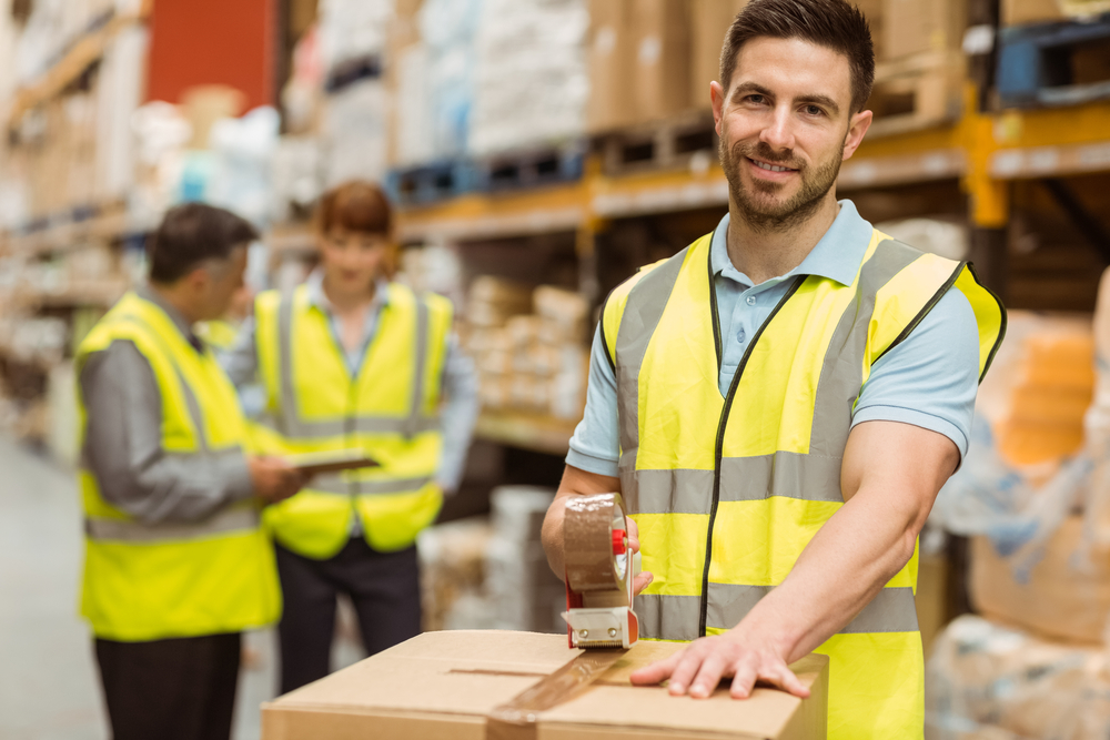 Smiling warehouse workers preparing a shipment in a large warehouse